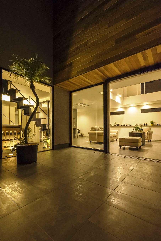 Hands Works(ハンズワークス)【デザイン住宅、趣味、インテリア】家の一部として取り込まれたプライベート感満載の中庭。リビングと同じタイルを敷き、一体感を演出している。軒や壁の無垢材、塗り壁との対比も絶妙