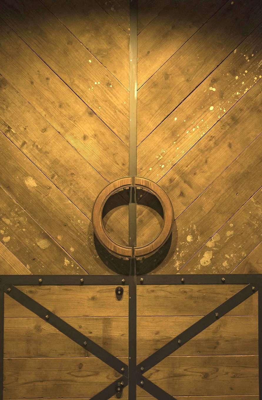 Hands Works(ハンズワークス)【デザイン住宅、趣味、インテリア】足場板で造作した玄関ドア。ラウンドの取っ手は木製。縁にアイアンをあしらう細かな細工が、デザインセンスや職人の技術の高さを物語る