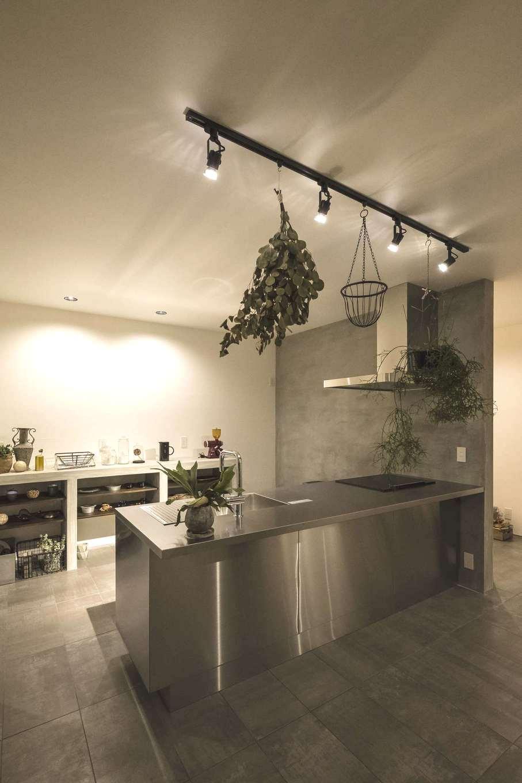 Hands Works(ハンズワークス)【デザイン住宅、趣味、インテリア】存在感のあるステンレスキッチンを主役に。サイドの壁はモルタル塗装で、床の質感とコーディネート。背面の収納棚もフレームはモルタルづくり、棚板は無垢材を用いた