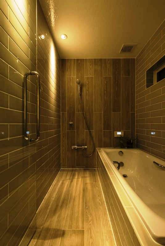 Hands Works(ハンズワークス)【デザイン住宅、インテリア、狭小住宅】洗面脱衣所との仕切りのタイルを浴室にも用いた造作。扉をガラスにして広がりを感じる空間に。ゆったりと足を伸ばして浸かれる浴槽もこだわりポイント