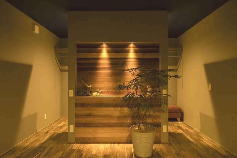 Hands Works(ハンズワークス)【デザイン住宅、インテリア、狭小住宅】ベッドのヘッドボードを兼ねる壁には、シンプルな棚とダウンライトを。後ろは回遊できるウォークインクローゼット。左右で夫婦が使い分けられる