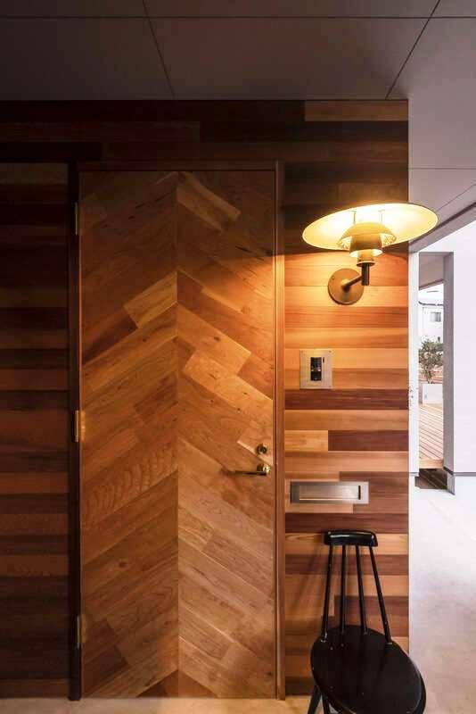 Hands Works(ハンズワークス)【デザイン住宅、インテリア、狭小住宅】玄関周りはレッドシダーの乱尺張りに。色の濃淡が絶妙なニュアンスを醸し出す。玄関ドアは、ノブや鍵の質感にこだわって選んだ。対面にはご主人のゴルフ道具や外で使うものを収納できる納戸がある