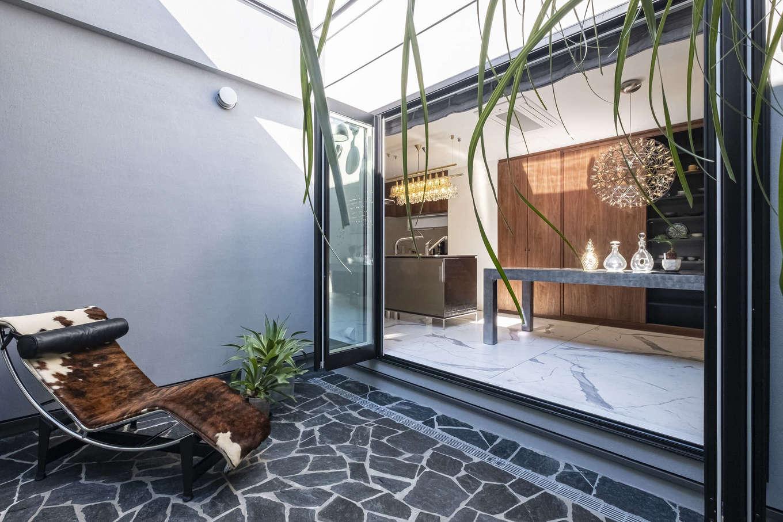 Hands Works(ハンズワークス)【デザイン住宅、自然素材、高級住宅】外からの視線を遮りながら、開放的に過ごせる中庭。ダイニングの全開口サッシを開けると、外と中との一体感が生まれる