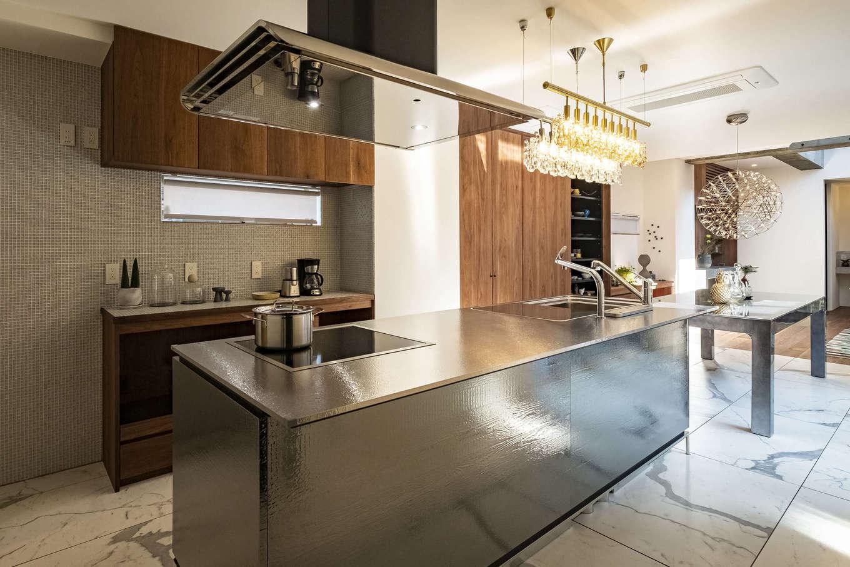 Hands Works(ハンズワークス)【デザイン住宅、自然素材、高級住宅】キッチンと照明とダイニングテーブルは、「TOYO KITCHEN」でコーディネート。ラグジュアリーな雰囲気に合わせて床に磁器タイルを貼った。料理をしながら、中庭で遊ぶ子どもたちの様子も見える