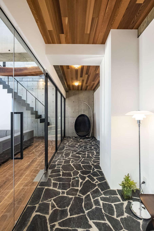 Hands Works(ハンズワークス)【デザイン住宅、自然素材、高級住宅】ポーチから中庭の前を通り、玄関ホールへ。石英岩の床が高級感を演出し、訪れるゲストの高揚感を誘う。天井のレッドシダーとのコントラストもすてき