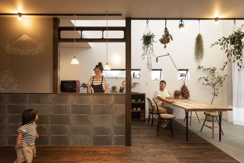 Hands Works(ハンズワークス)【子育て、自然素材、インテリア】吹抜けのLDK。土間のダイニング、CBブロックのキッチン、古民家の欄間がバランス良く融合し、古民家のカフェのような雰囲気を醸し出している。グリーンのディスプレイがおしゃれ