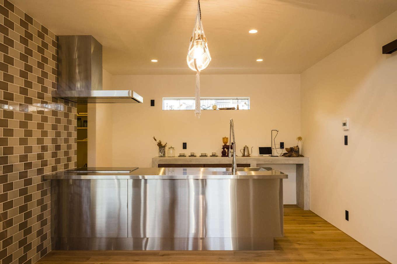 奥さまがどうしても欲しかったオールステンレスのオープンキッチン。カフェの厨房のようなデザインと使いやすさがお気に入り。食器棚は造作。奥には広いパントリーも完備している