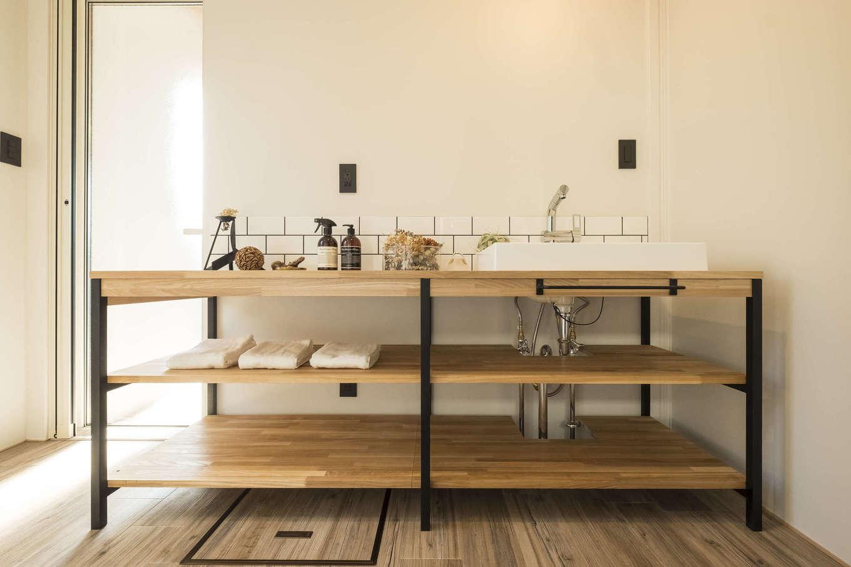 オリジナル造作の洗面台。フレームタイプのデザインでタオルや生活雑貨を見せる収納は、出しやすくしまいやすいのが特徴。サブウェイタイルとの相性も抜群だ。ここから脱衣室、サンデッキへとつながる動線が便利