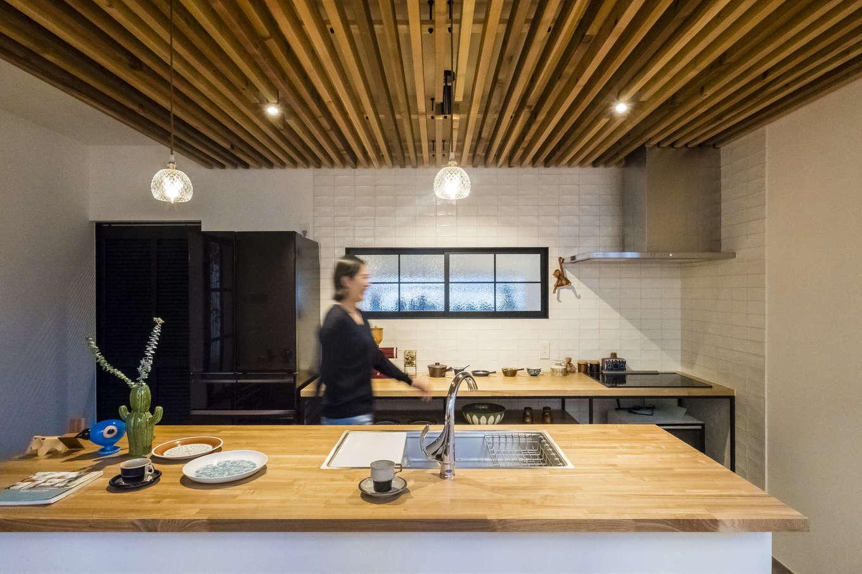 Hands Works(ハンズワークス)【デザイン住宅、収納力、自然素材】シンクとコンロを分けたセパレート型のキッチンを造作。ダイニング兼用として使うスタイルで、家族のコミュニケーションもスムーズ。天井の木格子がおしゃれなアクセントに。アイアンの窓枠をつけたバックヤードは広いパントリー