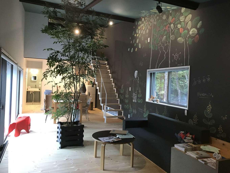 Hands Works(ハンズワークス)【1000万円台、趣味、平屋】21畳のLDKは、別荘として使うには十分な広さ。天井が高いため、さらに開放感が増し、ゆったりと寛げる。黒板クロスに描かれた樹木の絵はピンスポットで照らし、インテリアとして楽しむ。階段で上がるロフト付き