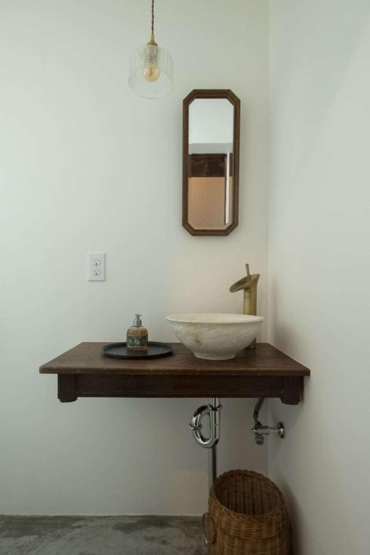 おしゃれな空間に一新されたトイレ内の洗面コーナー。陶器の洗面ボウルは施主さんの手づくり