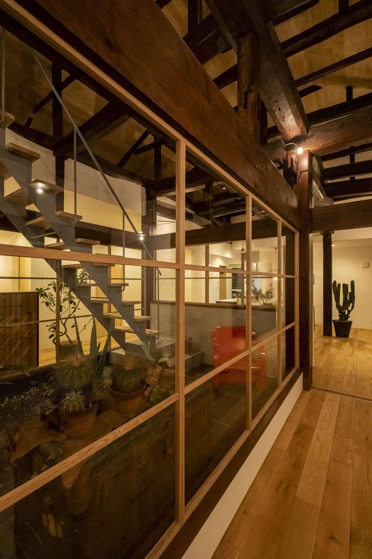 中庭に面した玄関ホール。細く緊張感のある木の窓枠は『Hands Works』のオリジナル造作。空間を引き締めつつも、手しごとならではの味わいが雰囲気を添える