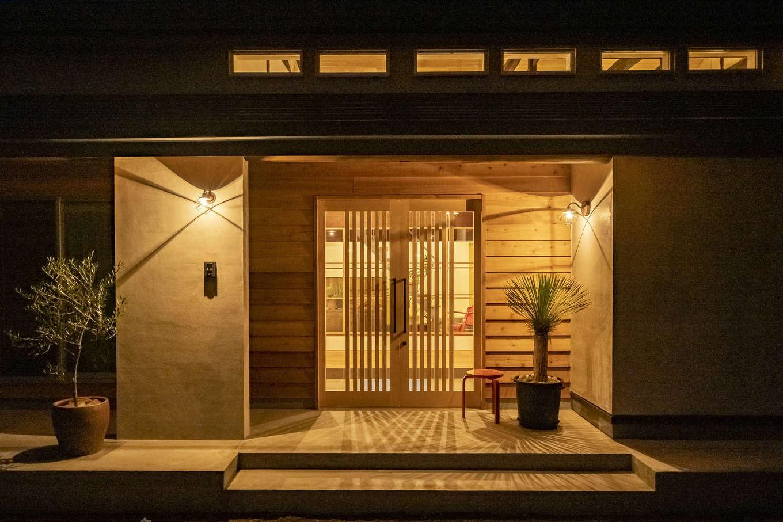京町屋のような風情が漂う、趣のある玄関。軒天と壁に無垢板を張り、ニュアンスを出した。造作の引き戸が高級感を演出。照明の陰影効果まで計算されている
