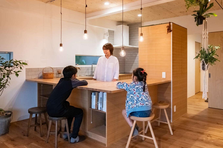 コの字型の造作キッチンは、ダイニングテーブル兼用のカウンター付きでコミュニケーションをとりやすい。冷蔵庫を造作の木製BOXで隠し、生活感を出さない工夫もポイント
