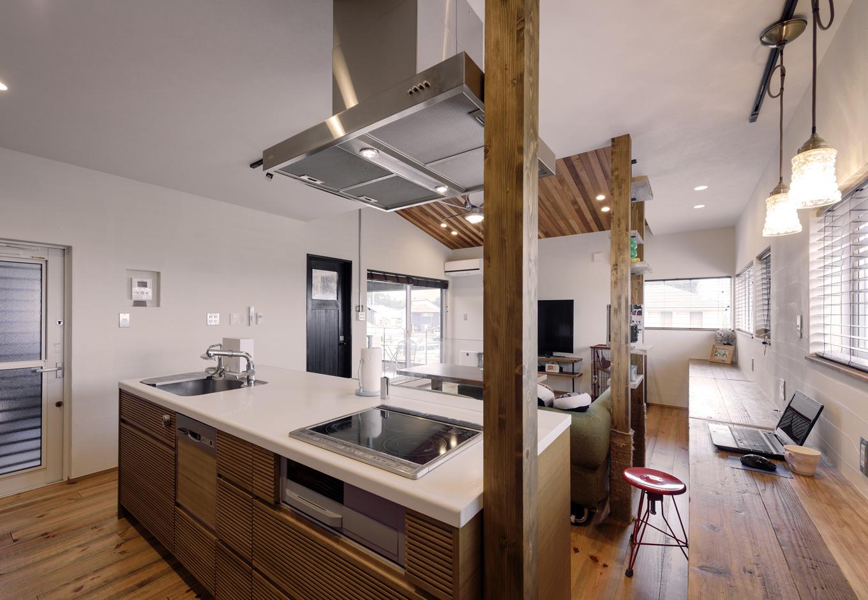 R+house 浜松中央(西遠建設)【デザイン住宅、建築家、インテリア】キッチンは「アール・プラス・ハウス」のオリジナル。対面式で室内全体が見渡せる。隣のカウンターには工事用の足場板を使用。ヴィンテージ感漂う室内にぴったりマッチしている。左側のドアは生ゴミなどを出しておけるサービスバルコニーへと続く