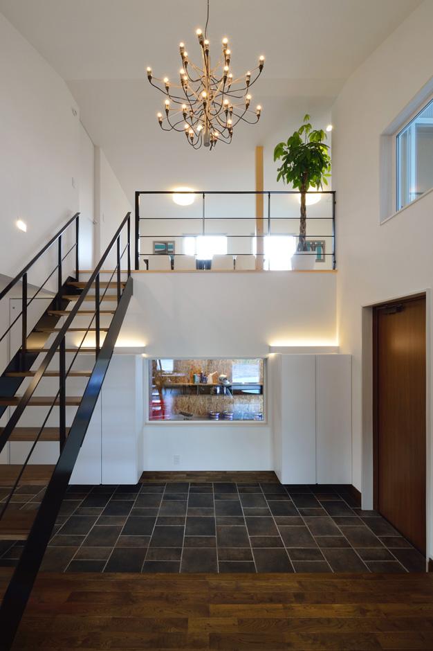 R+house 浜松中央(西遠建設)【デザイン住宅、建築家、インテリア】オープンな吹抜けの玄関。土間をまたぐようにストリップ階段を大胆に架け、玄関収納の合間にインナーガレージの見える大きなフィックス窓を配置