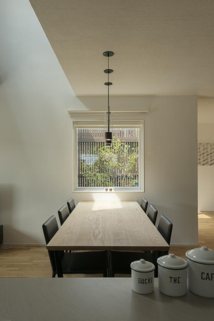 R+house 浜松中央(西遠建設)【デザイン住宅、インテリア、建築家】キッチンとダイニングの正面に四角の窓があり、まるで絵画のように空や緑が映りこむ