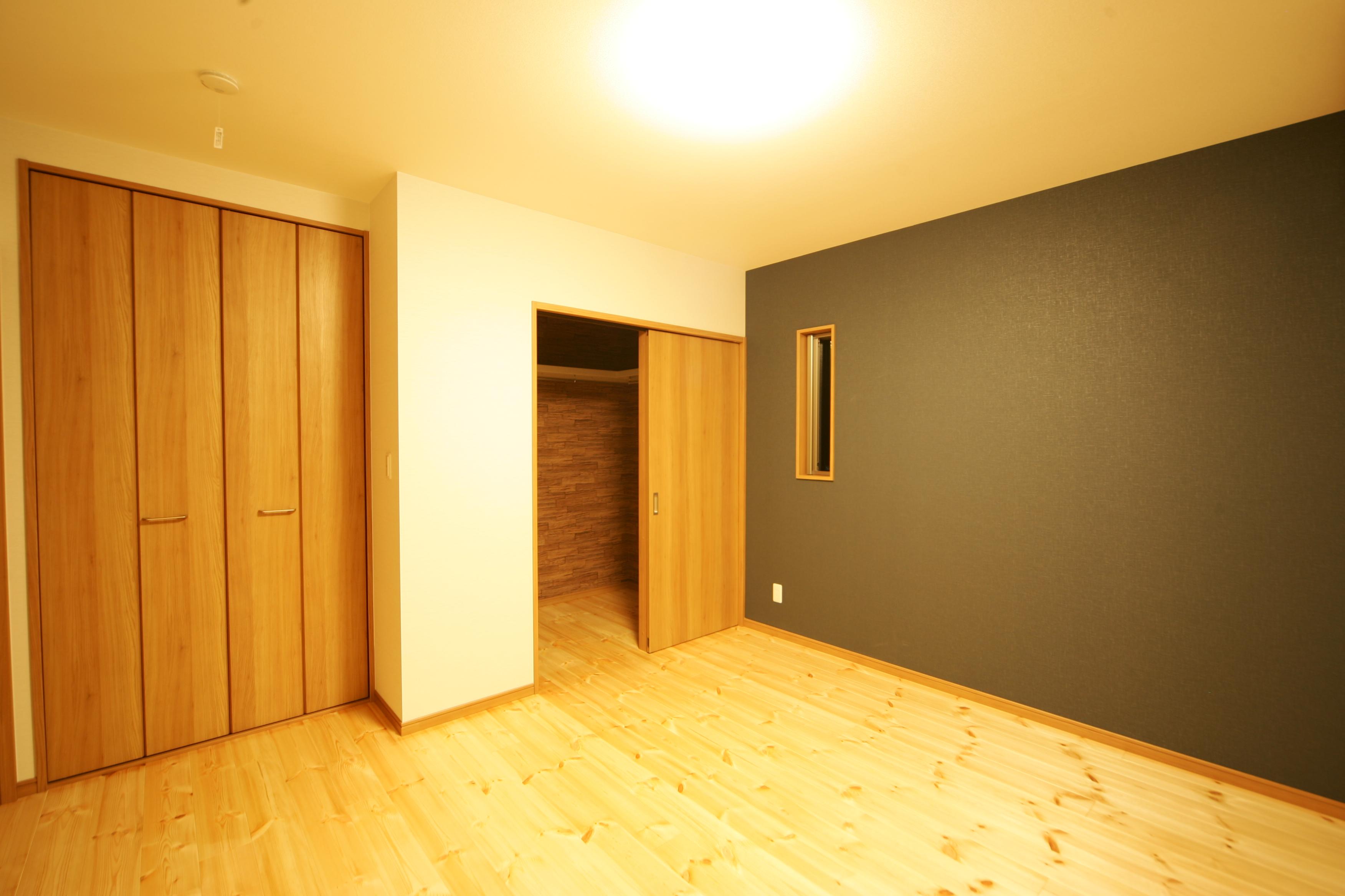 住まいるコーポレーション【子育て、自然素材、間取り】モスグリーンのアクセントクロスが、落ち着いた雰囲気をかもしだす夫婦の寝室。ウォークインクローゼットと納戸を設けてあるので、衣類や荷物がすっきり片付く