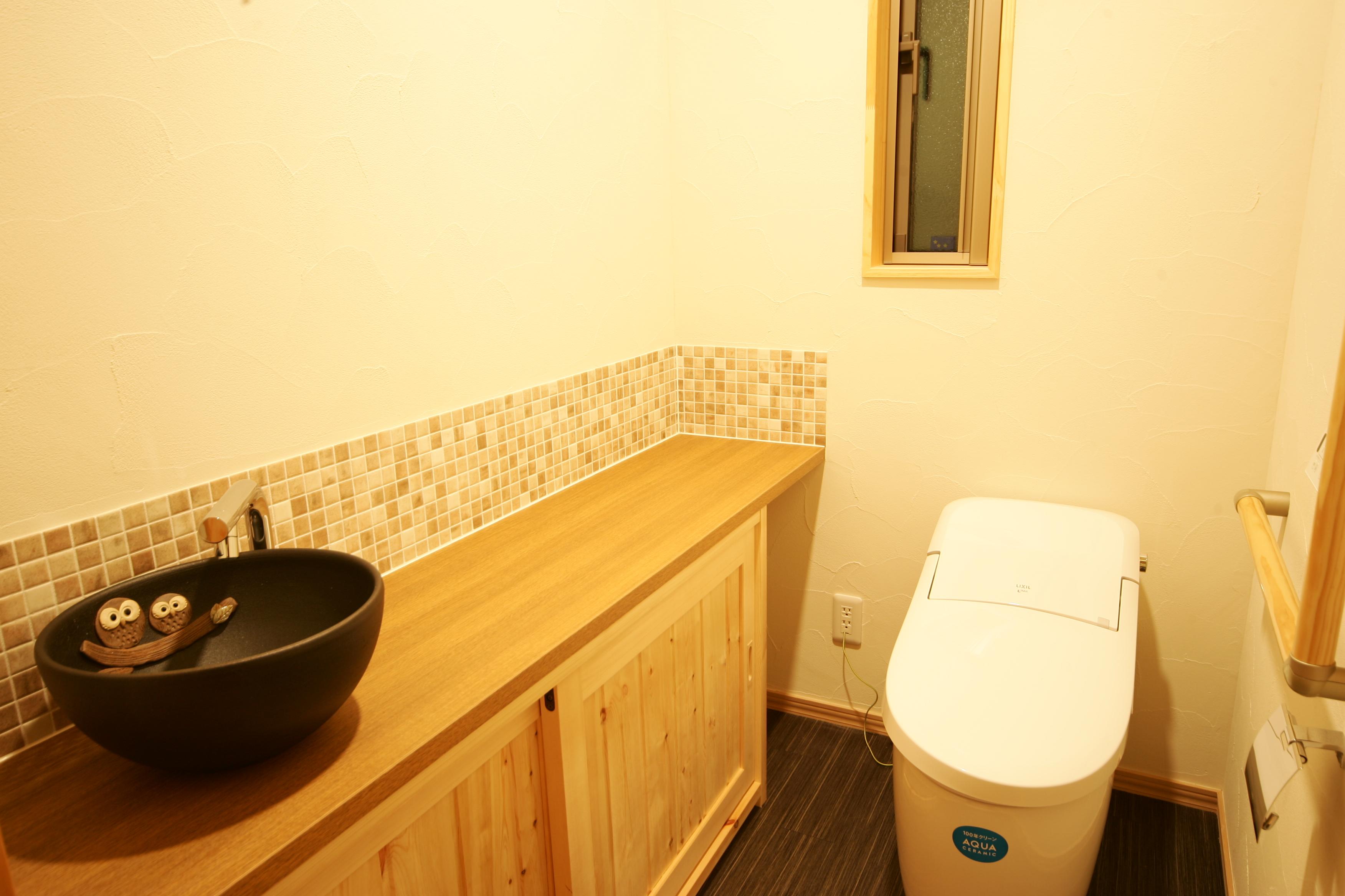 住まいるコーポレーション【子育て、自然素材、間取り】トイレの手洗いカウンターは、信楽焼きとモザイクタイルで和モダン風にコーディネート。収納スペースもたっぷり確保した