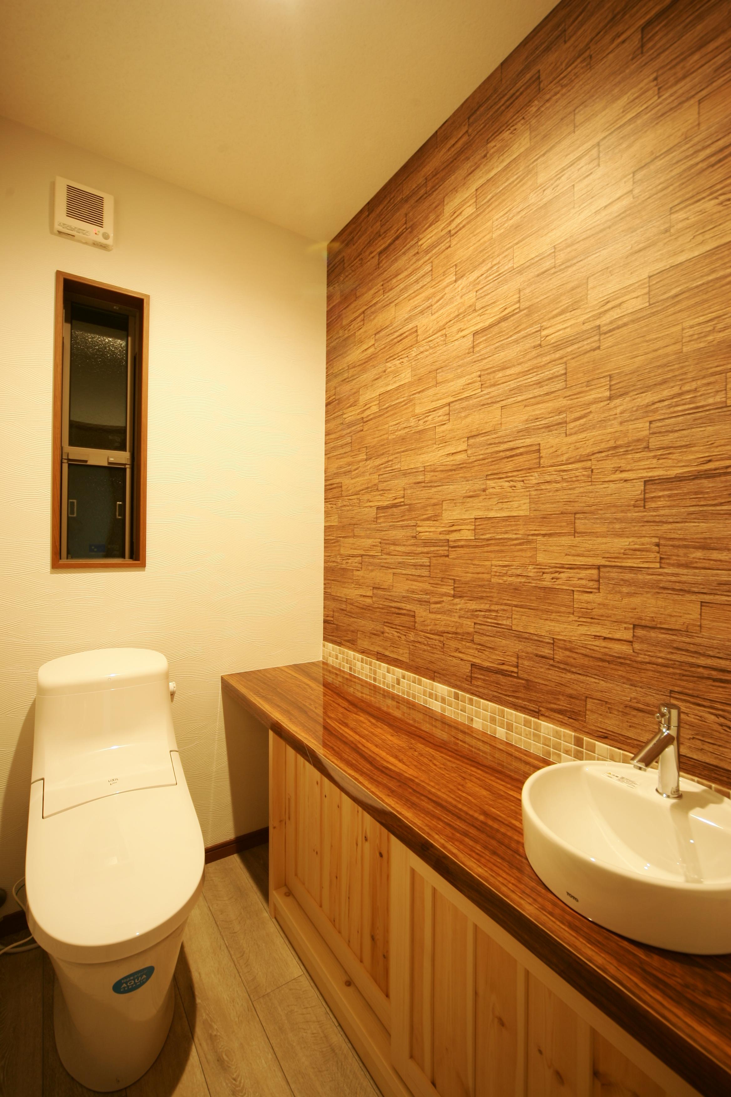 住まいるコーポレーション【子育て、自然素材、間取り】トイレのカウンターにはカリンの鏡面仕上げを用い、個性的で洗練された空間にデザイン。壁のクロスや床のクッションフロアのコーディネートにもこだわりが感じられる