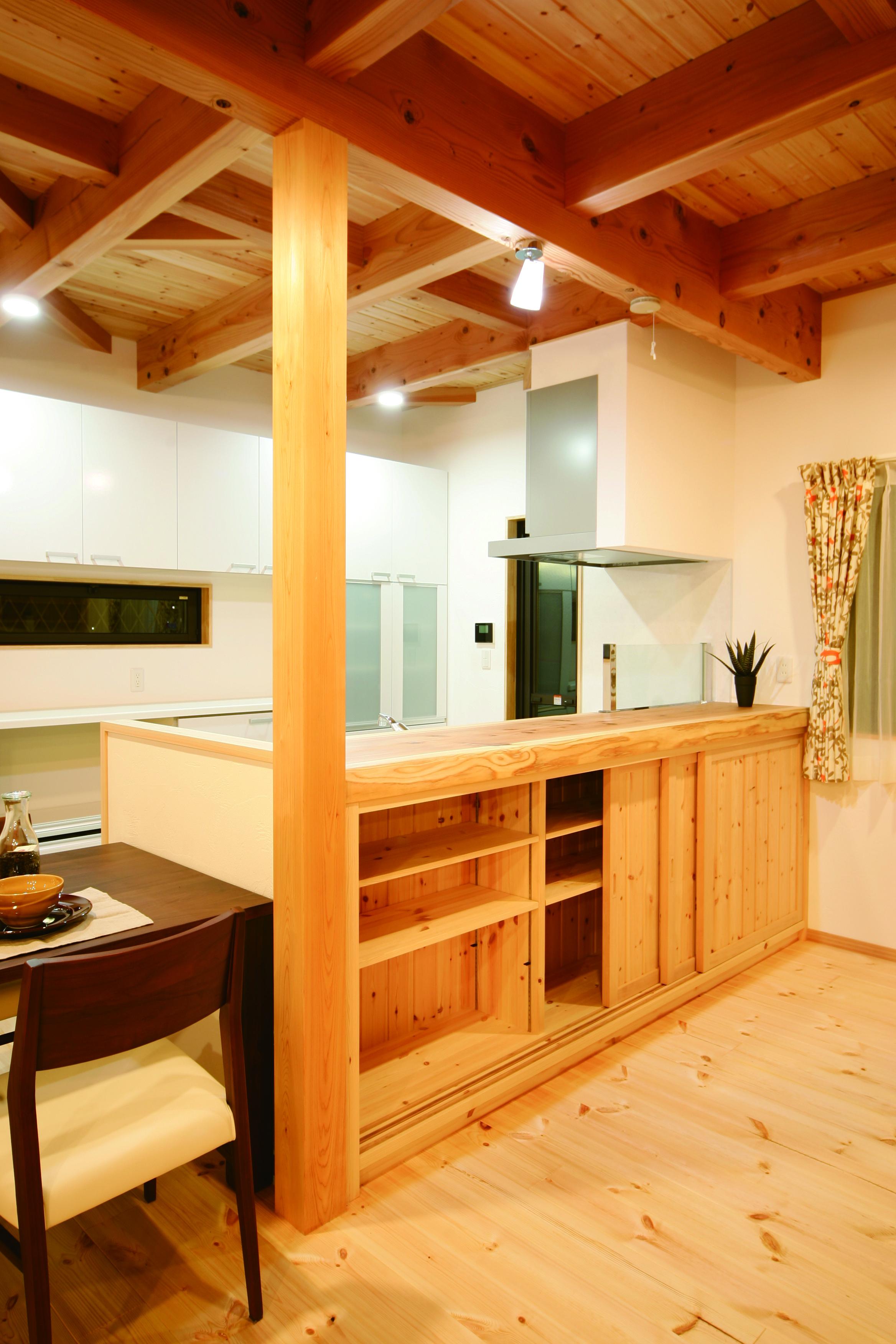住まいるコーポレーション【子育て、収納力、自然素材】対面キッチンのカウンターは温かみのある杉を使用。造作の収納棚もたくさん設けてある。キッチンスペースにゆとりを持たせてあるので、ご主人と2人でキッチンに立つときも動作がスムーズにできる