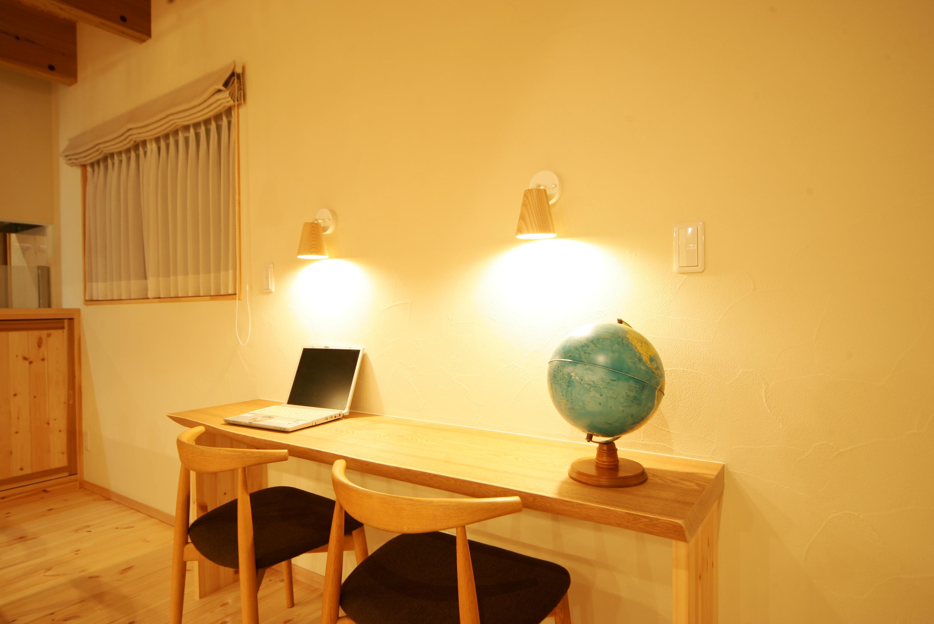 住まいるコーポレーション【子育て、収納力、自然素材】子どもたちのスタディコーナーは、オリジナルデザインのシンプルなカウンターに。スポット照明も2つ設けてある。奥さまがキッチンで調理や片付けをしながら、子どもの勉強を見てあげることもできそう。アイロンがけやPC作業など、多目的に使用可能