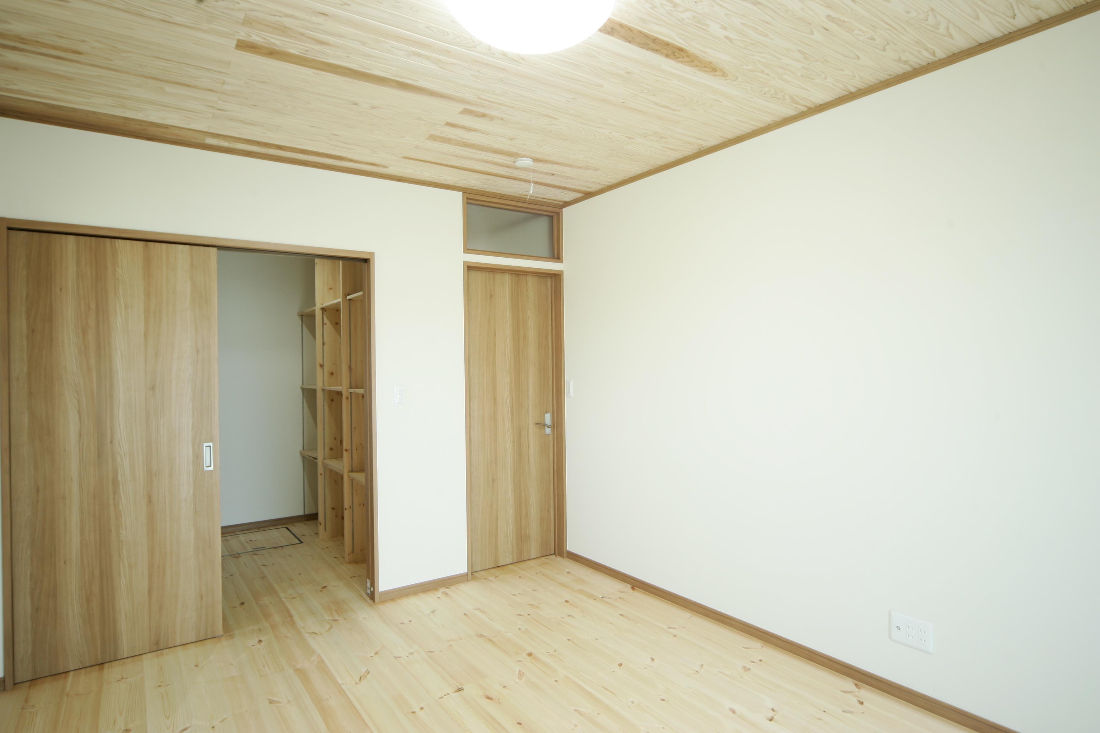 住まいるコーポレーション【二世帯住宅、自然素材、平屋】夫婦の寝室。ウォークインクローゼットにはハンガーと可動棚のコーナーを左右に分け、洋服や小物を出し入れしやすいように工夫した