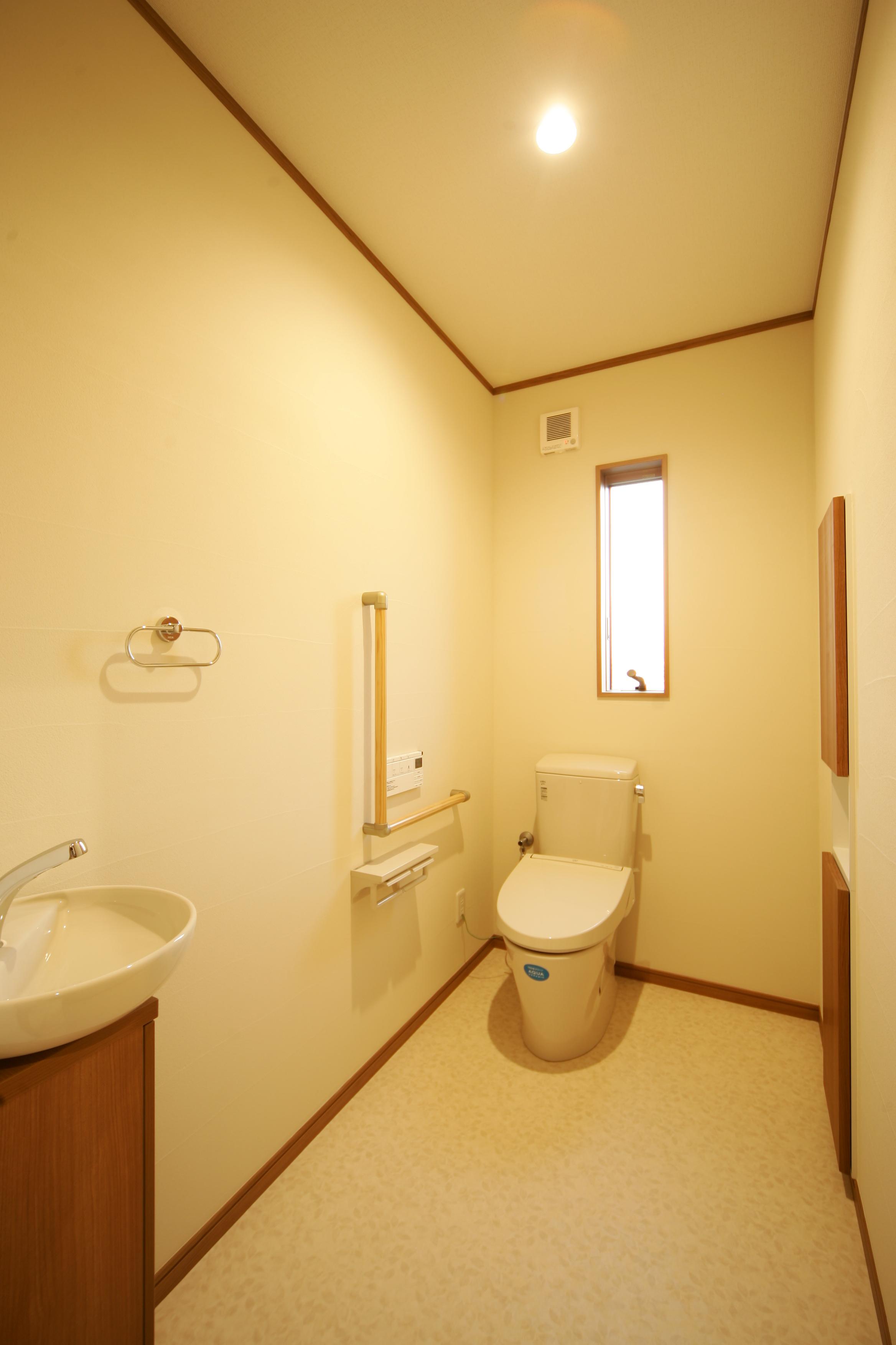 住まいるコーポレーション【二世帯住宅、自然素材、平屋】トイレも通常よりも広さにゆとりを持たせ、手すりもしっかり設けてある。湿気がこもらないように、壁には珪藻土を使用