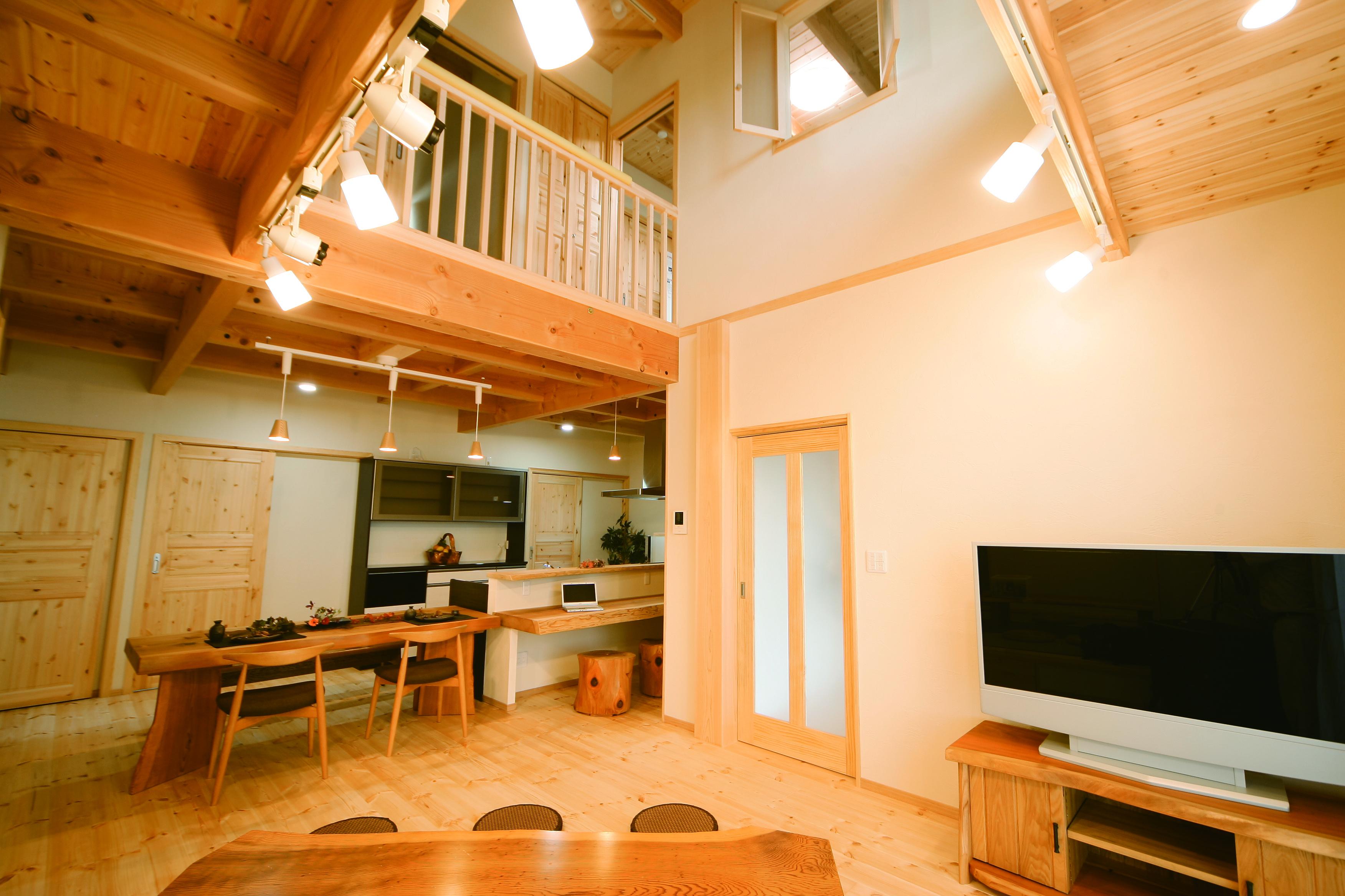 住まいるコーポレーション【和風、自然素材、省エネ】大きな吹抜けのあるLDK。珪藻土とパインのおりなす自然素材の空間は、梅雨の季節でも涼しく快適。床や天井のパイン材はナチュラルで優しいトーンと個性的な木目が特徴。2階の個室と寝室には小窓を設けてあり、1階を見下ろしたり、家族に声をかけたりすることもできる