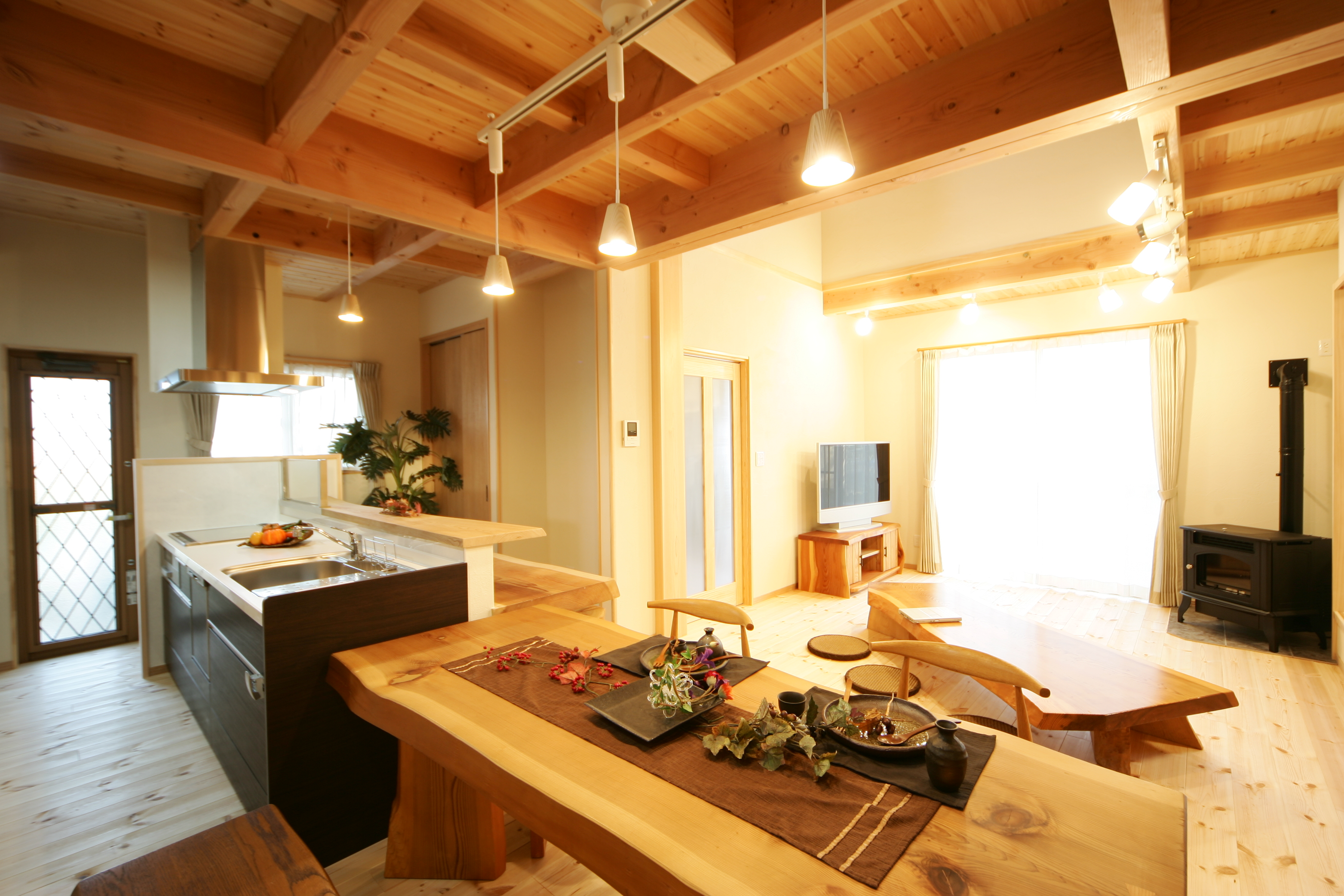 住まいるコーポレーション【和風、自然素材、省エネ】キッチンとダイニングテーブルを一列に並べ、配膳や片付けが格段と便利に。リビングにはペレットストーブがあり、冬は家中が心地よく暖まる