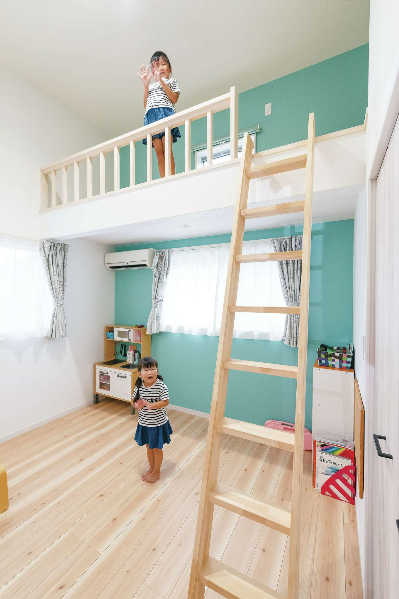 子ども部屋は左右対称に用意。床や建具の色合いも、壁に合わせて明るいものを選んだ。あいだには、かくれんぼのときに活躍しそうな物入れが用意されている。ポップでかわいいティファニーブルーは、奥さまによるセレクト