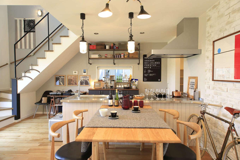 エムデカーサ/10taku+【デザイン住宅、趣味、平屋】フロア全体が見渡せる対面型のキッチン。背面の壁に造りつけたハイセンスなアイアン棚も標準仕様。また、キッチン横には食品やキッチン用品をたっぷり収納できるパントリーも