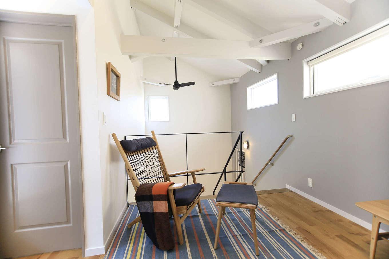 エムデカーサ/WOODBOX富士【デザイン住宅、趣味、平屋】2Fの共有ホールから見える吹き抜け上の天井。勾配をうまく使って仕上げている。構造材を兼ねた大きな梁が『WAREHOUSE』らしさを演出