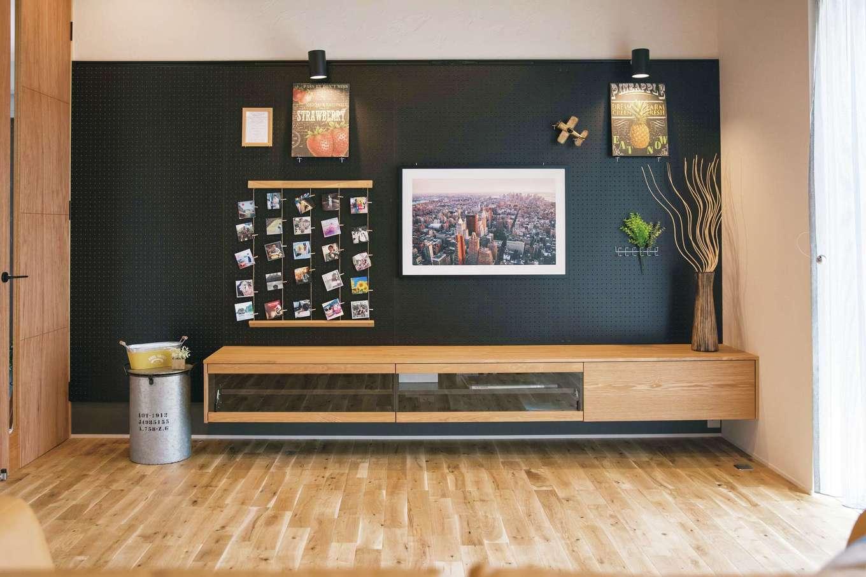 幹工務店【浜松市浜北区油一色176-1・モデルハウス】リビングの壁には黒いパンチングボードを使用。フックを使って好きな位置に棚や額を付けられる。宙に浮いた造作のTVボードは『幹工務店』のオリジナル