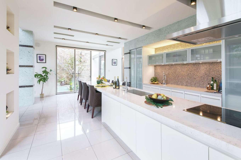 デザインハウス【浜松市南区青屋町400・モデルハウス】ダイニングテーブルと一体化したキッチンの天板には、デザイン性と耐久性に優れたクオーツストーンを採用。中庭の景色が、食事をより楽しいものにしてくれる