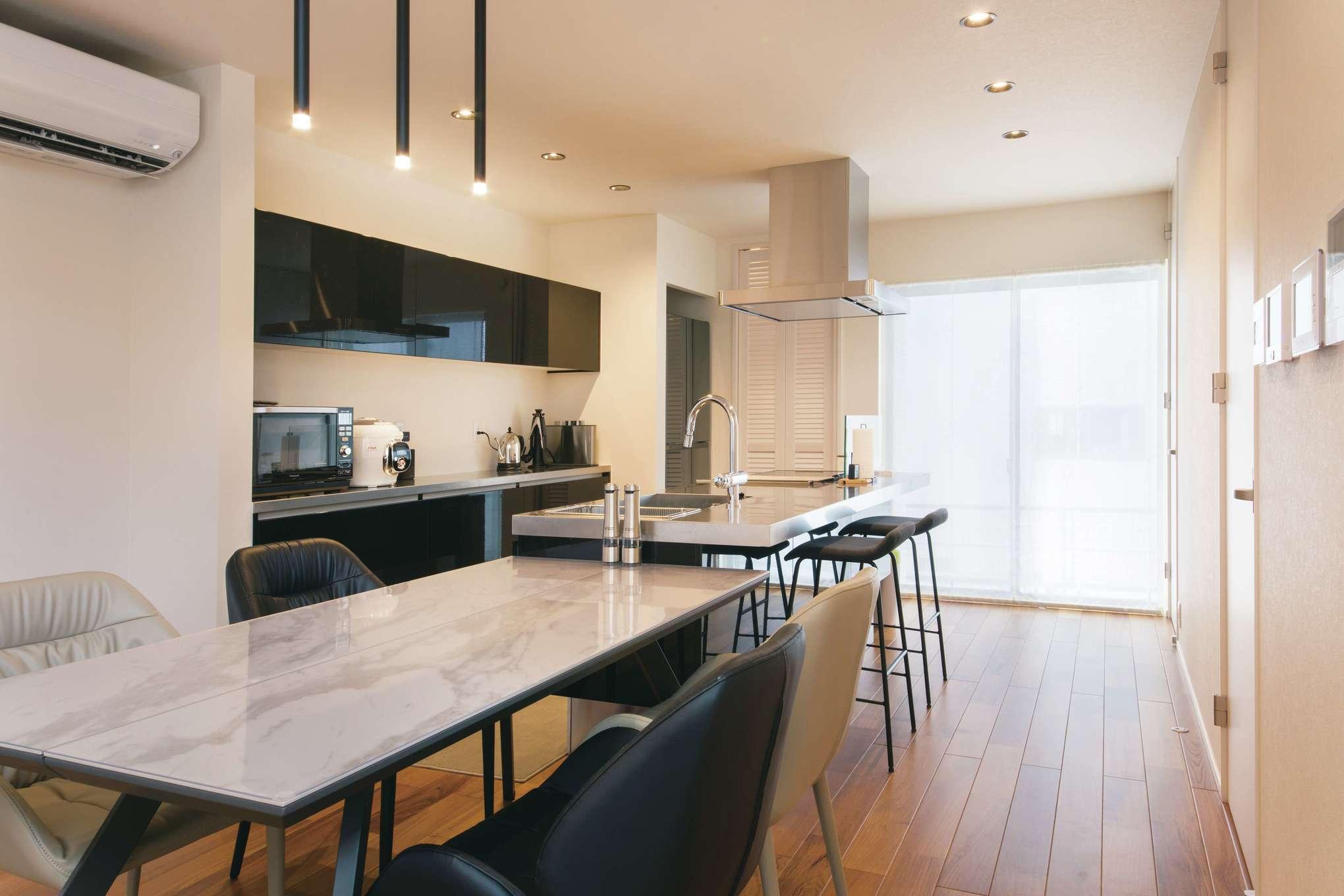 幸和ハウジング【デザイン住宅、屋上バルコニー、インテリア】スタイリッシュなキッチンは家電を含め、黒とステンレスでコーディネート。壁に収まる冷蔵庫やパントリーがあることで空間がスッキリとしている。正面に水回りを集約
