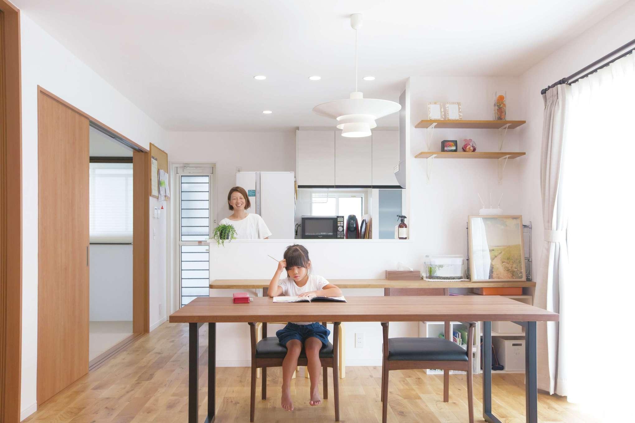 対面キッチンの前には木のカウンターと大きなダイニングテーブルがあり、キッチンからいつでも家族の様子を見守れる。キッチンの隣には和室がある