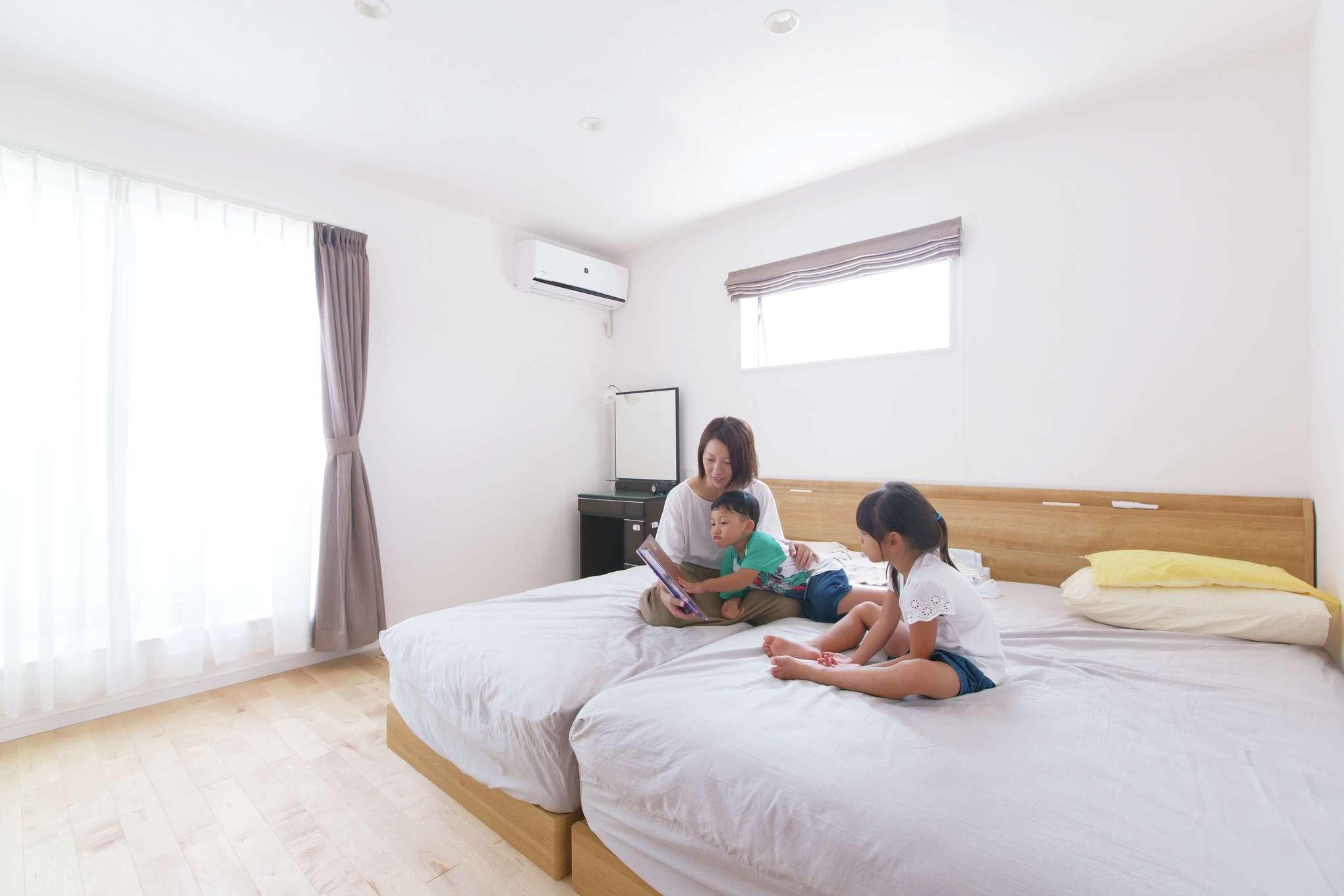 窓から柔らかな光が注ぐ広い寝室。自然素材に包まれて、ぐっすりと眠れるようになったそう