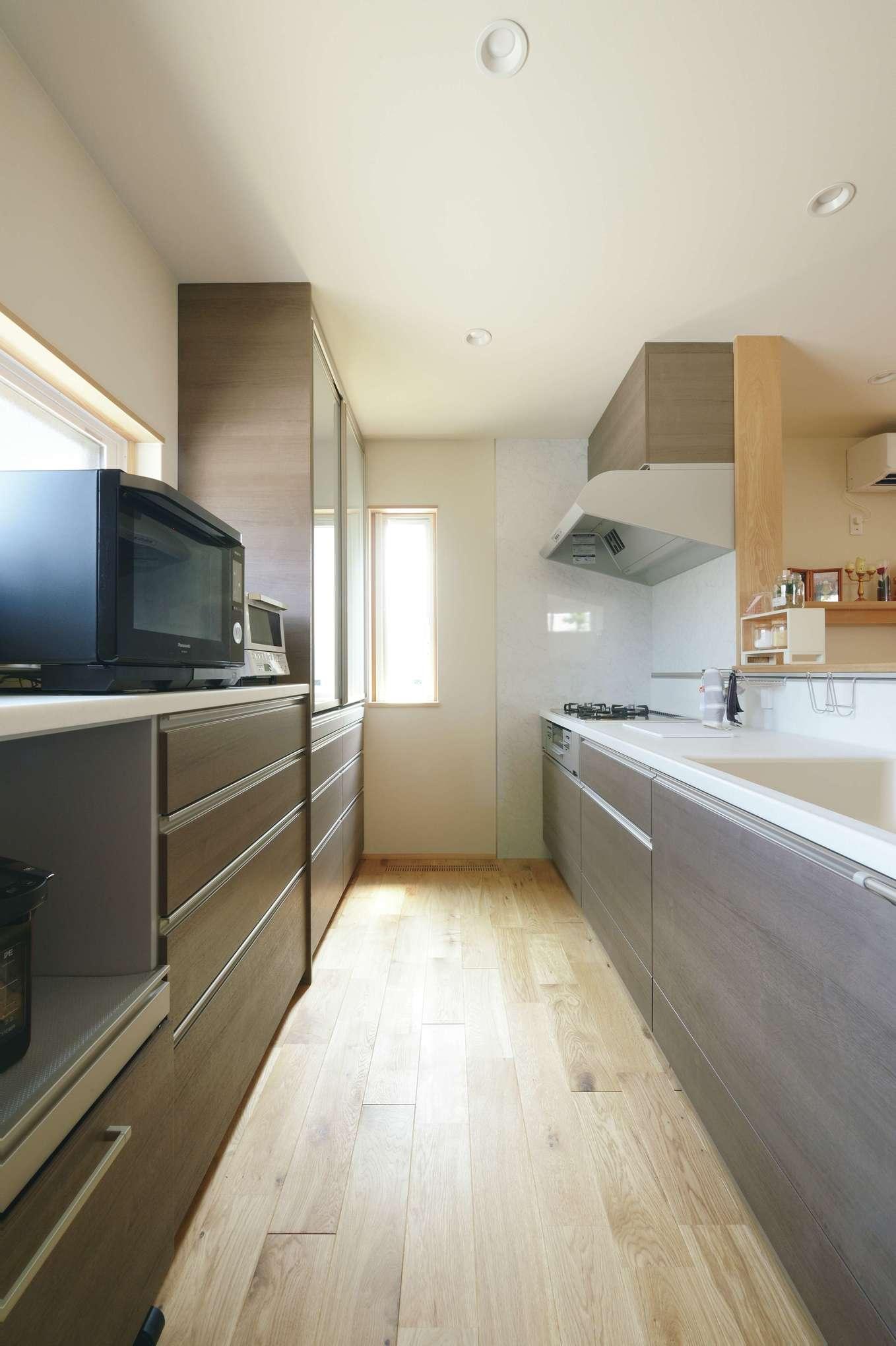 新栄住宅【自然素材、省エネ、間取り】大人が数人入っても窮屈に感じないキッチン。リビングからワークトップが見えないよう壁を高くした