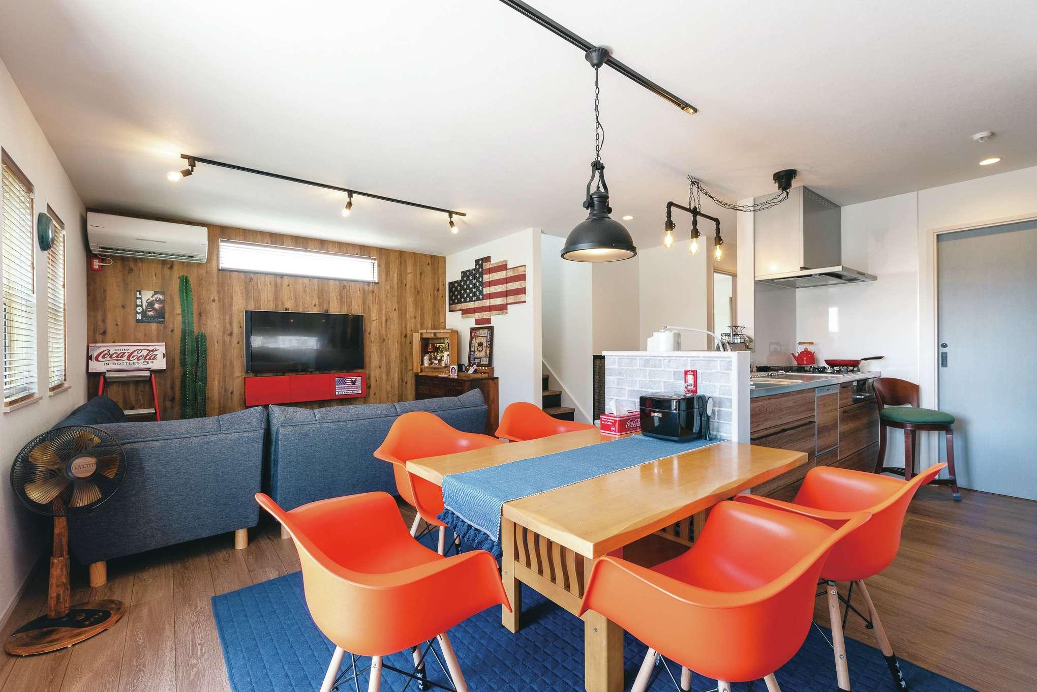 suzukuri 浜松店【デザイン住宅、インテリア、趣味】ビビッドなダイニングチェア、マットな質感のペンダントライト、タイル調のクロス、デニム地のソファなど、アメリカン&インダストリアルな雰囲気にコーディネートされたLDK