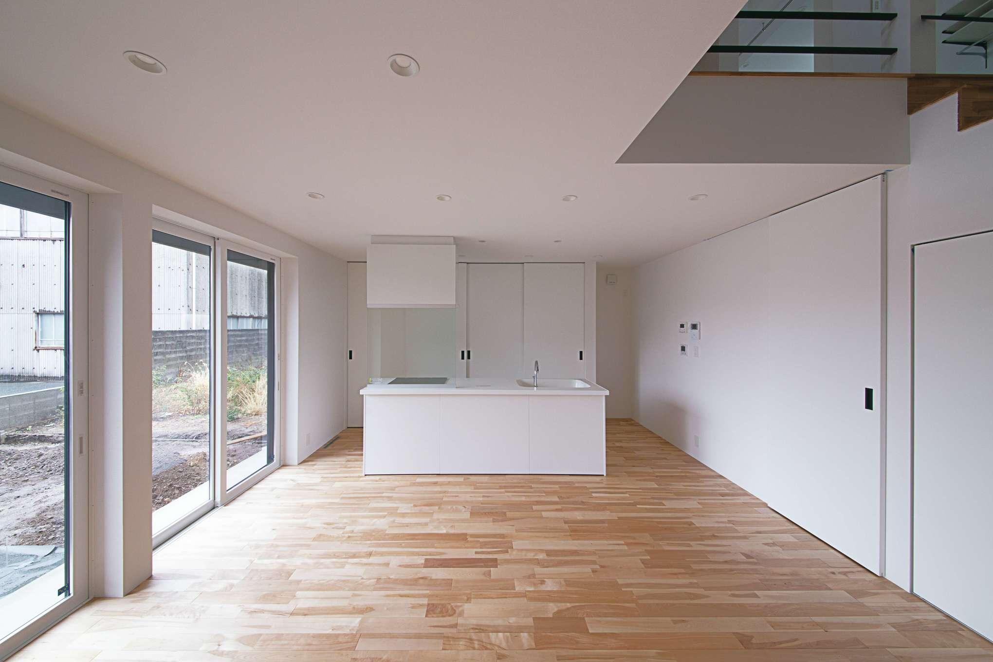 アイランドキッチンを中心に回遊動線を確保したLDK。キッチンの背面が収納になっている。室内の床はカバザクラ。無垢の上質感がワンクラス上の空間を演出