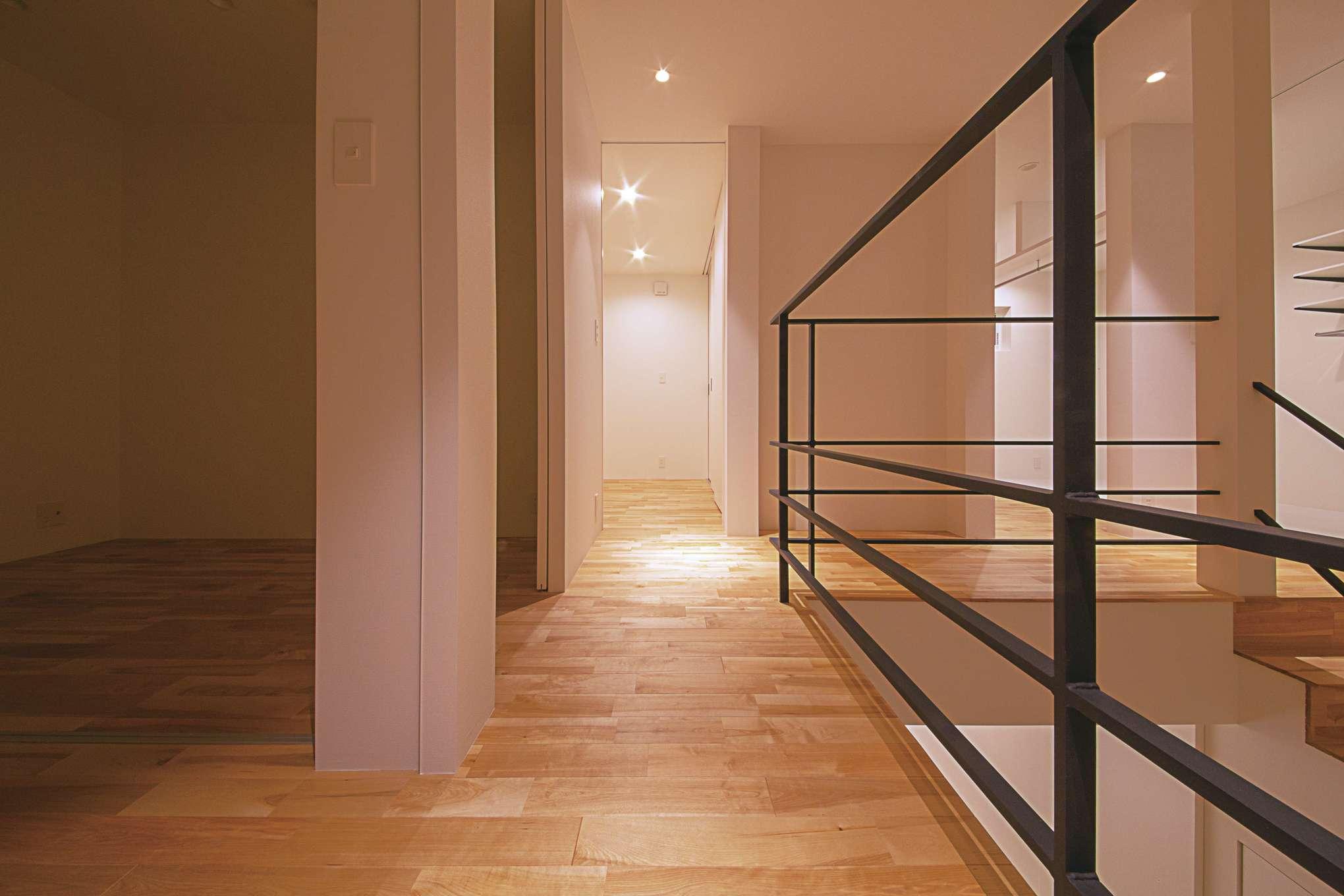 インフィルプラス【デザイン住宅、収納力、間取り】2階の各室を繋ぐ廊下。アイアンの手すりと吹抜けが開放感をもたらしている。階段を上がった正面がファミリークローゼット。隣は寝室