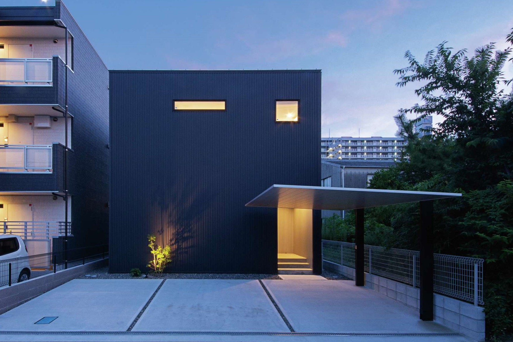インフィルプラス【デザイン住宅、収納力、間取り】モデルハウスの「MONO-house」をベースにデザインした箱型の外観。道路側の開口部は最低限にして、市街地でありながら十分にプライバシーを確保。ガルバリウム鋼板の外壁に灯りが豊かな表情をもたらしている