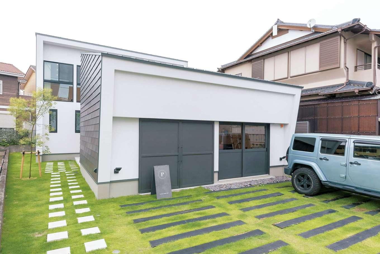 アンドエス【And.s】【デザイン住宅、高級住宅、インテリア】事務所側は基礎を斜めにして壁も斜めに。雨どいを隠してすっきり見せている。芝生に埋めた枕木はSさん自ら施工した