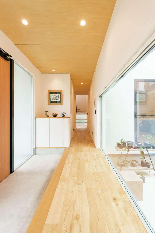 アンドエス【And.s】【デザイン住宅、高級住宅、インテリア】左右で自宅と事務所に分かれるワイドな玄関ホール。目の前には中庭が広がる
