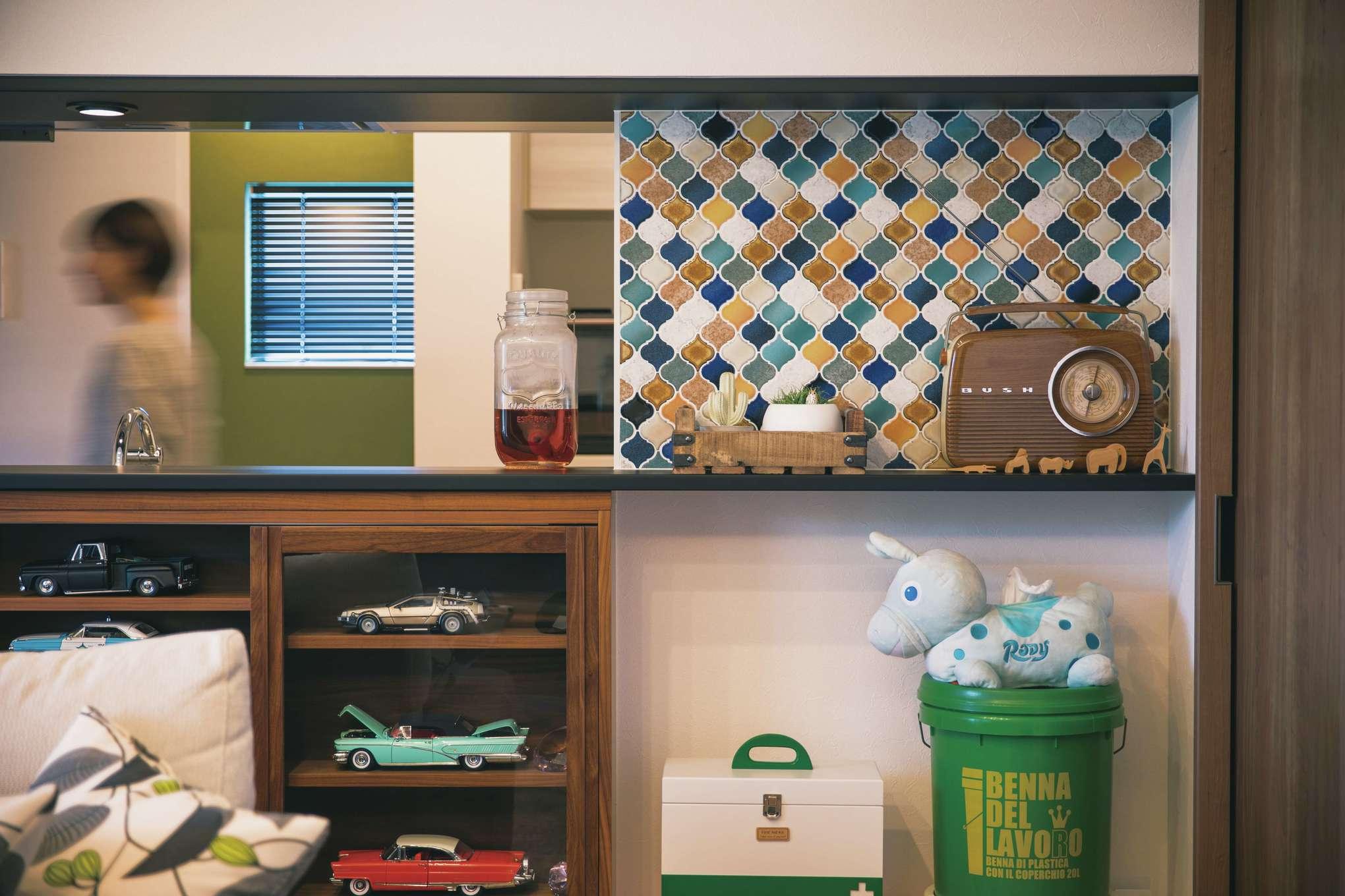 宮下工務店【デザイン住宅、間取り、インテリア】対面キッチンとの仕切り壁にはコラベルタイルを採用。カウンターの下にはぴったりサイズの棚にご主人のミニカーコレクションをディスプレイ