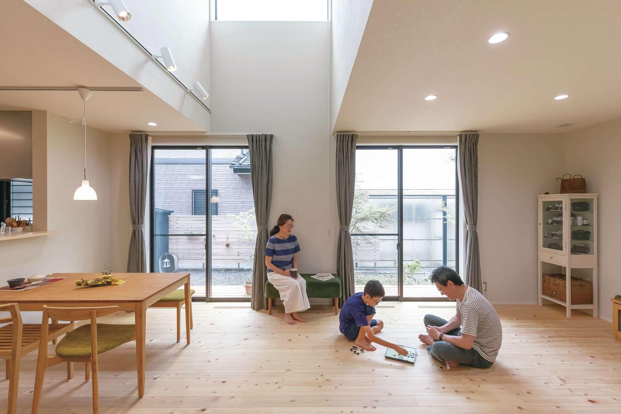 フジモクの家(富士木材)【デザイン住宅、子育て、自然素材】上質なヒノキの床とホタテペイントの壁に包まれた19畳のLDK。全館空調システムと自然素材の相乗効果により、家中の温度差がなく、空気がさらっとしている。ルイス・ポールセンのペンダントライトがシンプルな空間のアクセントに