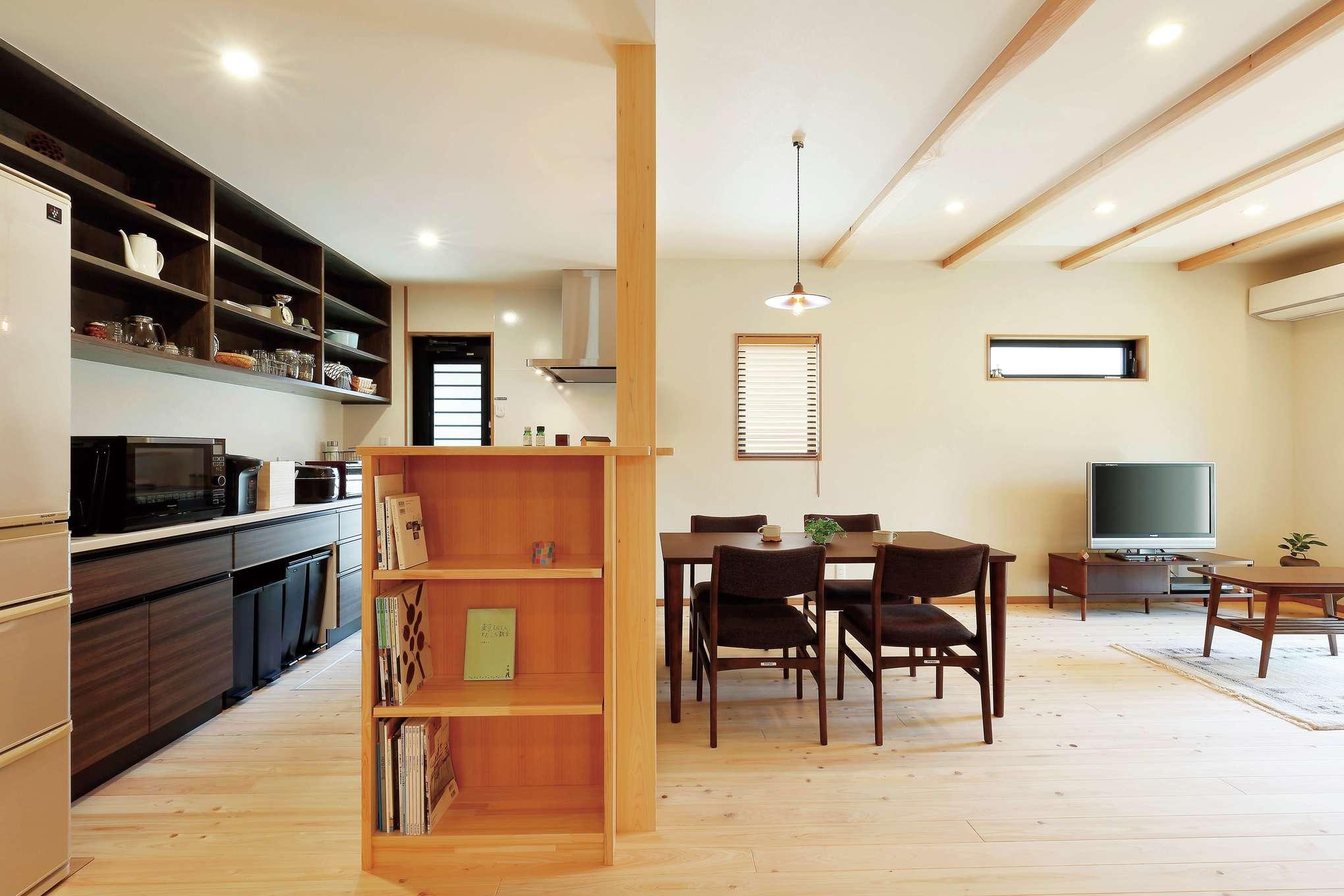 フジモクの家(富士木材)【デザイン住宅、収納力、自然素材】時間がゆっくりと流れるオール自然素材のLDK。ヒノキの床の経年変化も楽しみ。キッチンのデッドスペースを活かして本棚を造作し、食器棚の木の色を濃くしてアクセントをつけた