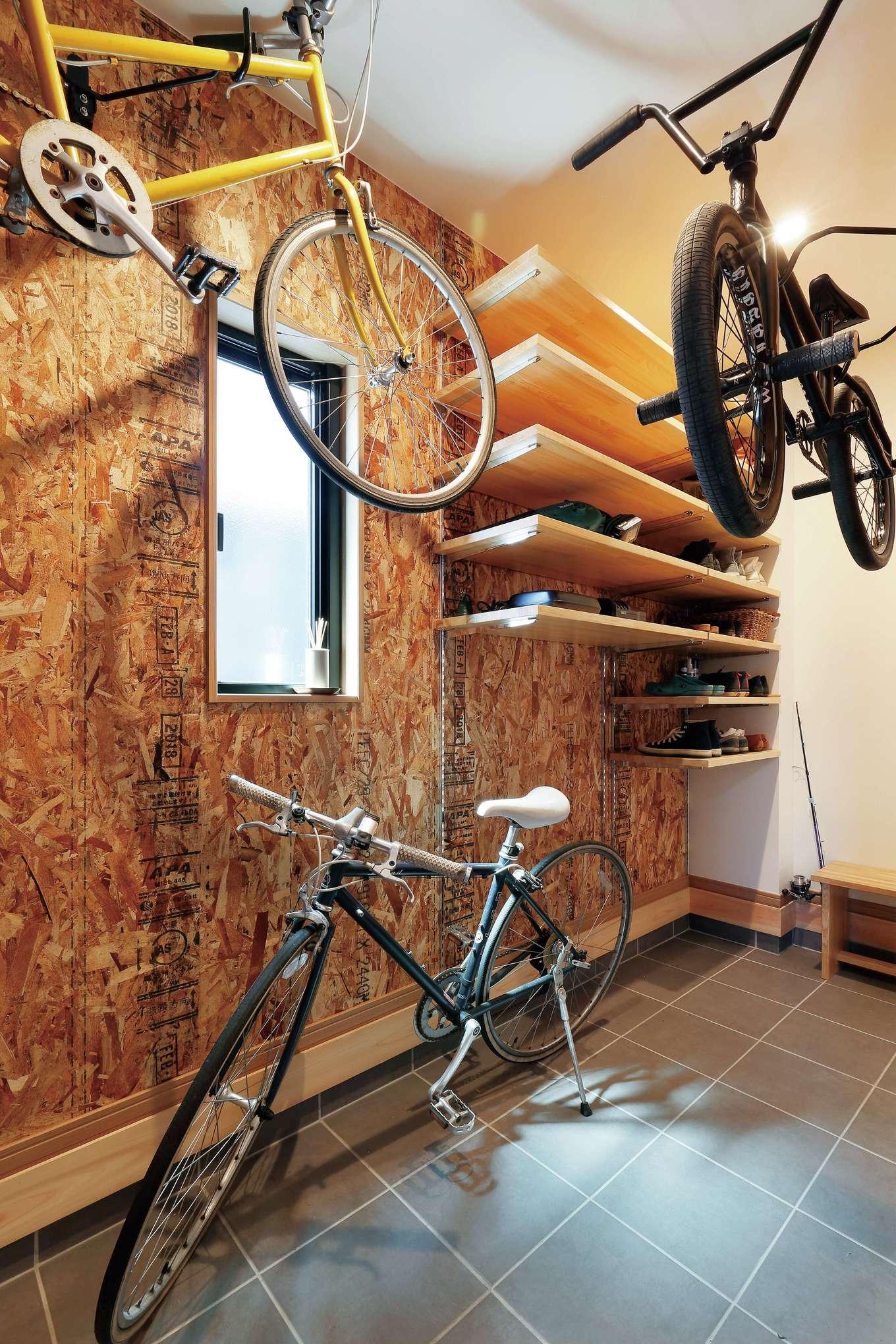 フジモクの家(富士木材)【デザイン住宅、収納力、自然素材】土間仕上げの玄関ホール。ご主人のBMXと奥さまの自転車を保管できる広さの収納を確保。OSB合板でワイルドにしつらえた