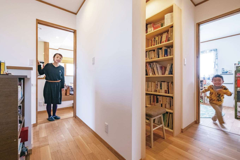 興友ハウス【子育て、間取り、狭小住宅】本棚は個室に設けず、家族みんなが活用できるようにオープンな図書コーナーに。ぐるりと回れて、移動も楽しい